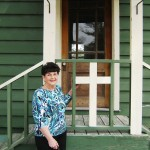 Judy Duda, long time Slavia resident in front of original church (photo - CMF Public Media)