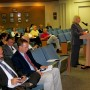 At podium, applicant Pam Carroll addresses city commission (photo - CMF Public Media)